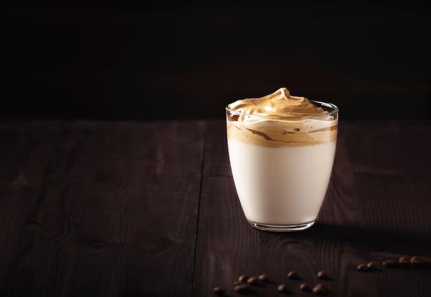Il caffè dalgona si trova in un bicchiere su un tavolo di legno scuro