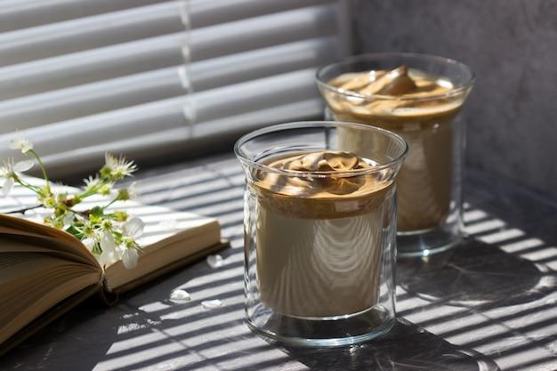 Dalgona coffee in bicchieri trasparenti su un davanzale illuminato dalla luce del sole.