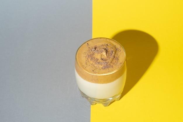 Caffè dalgona con schiuma rigogliosa in un bicchiere su uno sfondo giallo e grigio. bevanda coreana alla moda sui colori pantone di tendenza 2021.