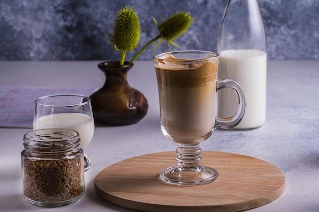 Dalgona espresso latte e ingredienti per la sua preparazione su un tavolo grigio. messa a fuoco selettiva.