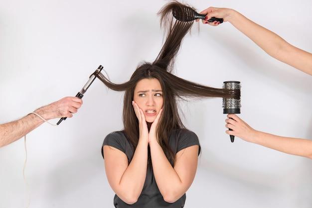 Concetto di capelli danneggiati, ragazza infelice con i suoi lunghi capelli asciutti e capelli danneggiati, isolato