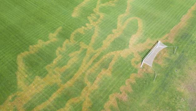 Erba del prato inglese danneggiata sul campo di calcio. vista dal drone. applicazione errata di fertilizzanti minerali o erbicidi. vandalismo sul campo sportivo.