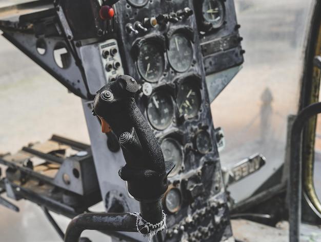 Cabina danneggiata del pannello di controllo dell'elicottero militare della vecchia guerra con scarsa illuminazione.