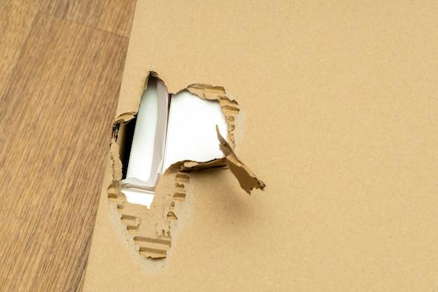 Confezione in scatola di cartone danneggiata e strappata con foro