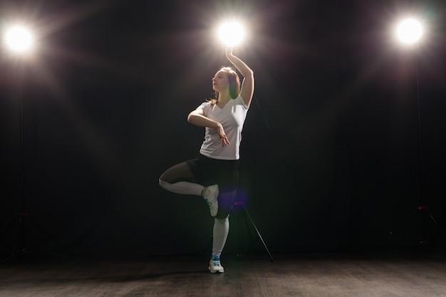 Danza, hip-hop, jazz funk e concetto di persone - giovane donna flessibile che balla nell'oscurità sotto la luce.