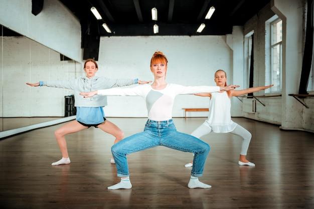 Lezione di ballo. insegnante di balletto sottile e bella indossa blue jeans facendo accovacciata con due giovani studenti