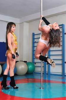 Formazione di danza di due donne su un palo, l'istruttore aiuta a mettere in posa