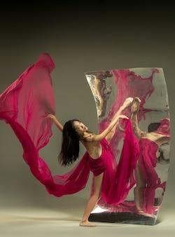 Danza con il fuoco. ballerina moderna sulla parete marrone con specchio. riflessi di illusione sulla superficie. magia della flessibilità, movimento con il tessuto. concetto di arte creativa danza, azione, ispirazione.