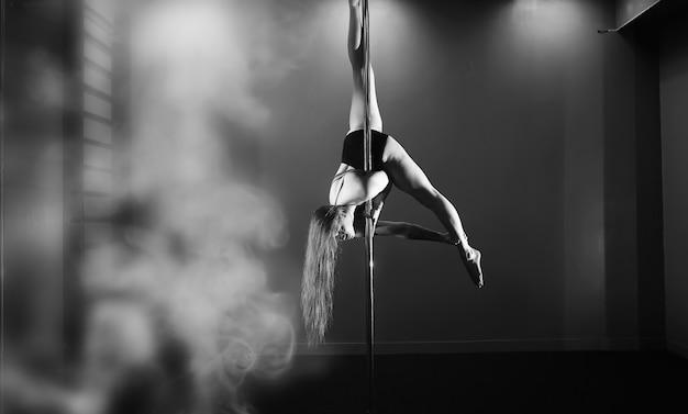 La ballerina sul pilone in studio. ragazza che fa esercizi su un'attrezzatura sportiva.