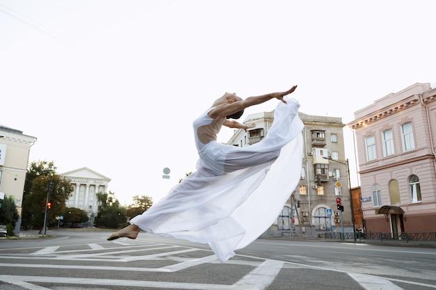 Ballerina in abito bianco salta