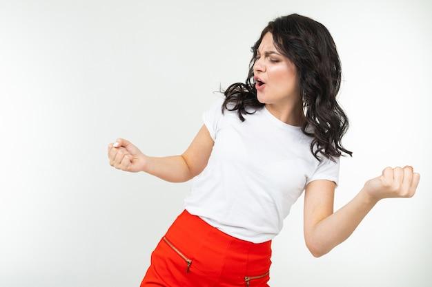 Dancing ragazza attraente in maglietta bianca isolata su uno sfondo bianco studio.