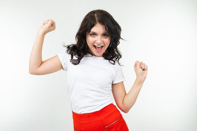 Dancing girl brunette in una maglietta bianca si stacca alla musica isolata su uno sfondo bianco.