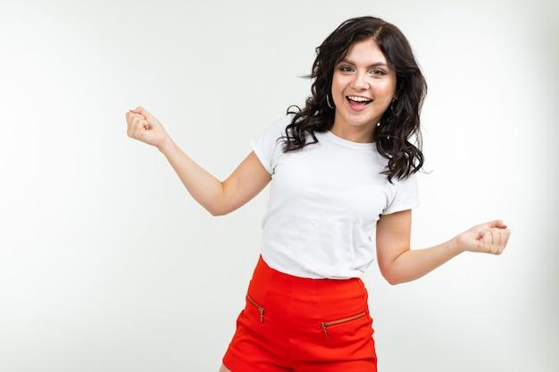 La donna castana di dancing in una maglietta bianca si stacca alla musica isolata su una priorità bassa bianca.