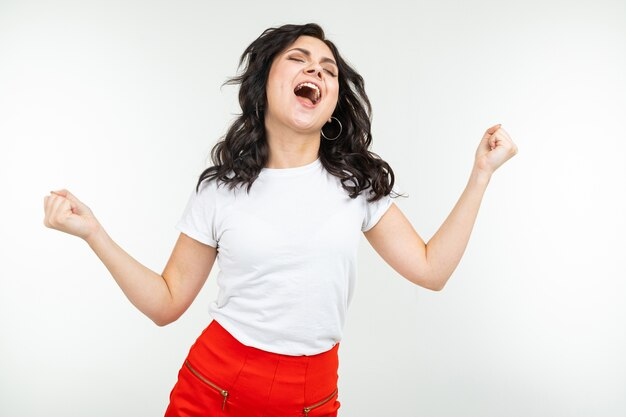 La donna castana che balla in una maglietta bianca si stacca alla musica isolata
