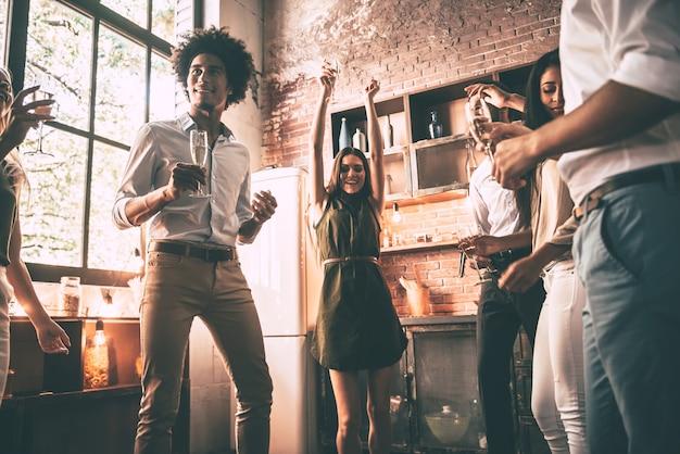 Ballare è tutto ciò di cui abbiamo bisogno! inquadratura dal basso di giovani allegri che ballano e bevono mentre si godono la festa a casa in cucina