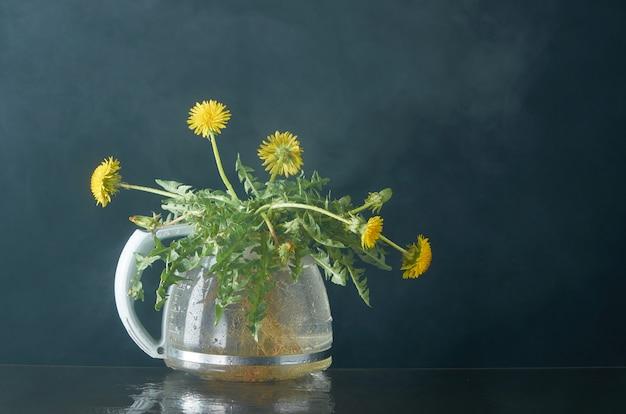Tarassaco con radici e foglie in una teiera di vetro su un buio in fumo