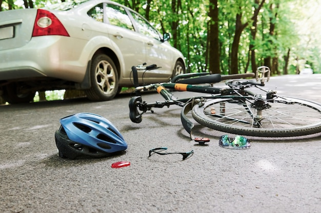 Luogo pericoloso. biciclette e incidente d'auto color argento sulla strada alla foresta durante il giorno