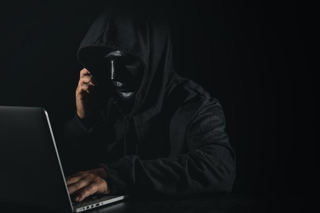 Uomo pericoloso hacker anonimo in incappucciato e maschera utilizzando computer e smartphone sul nero