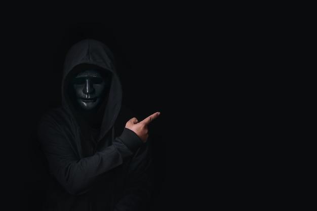Pericoloso hacker anonimo uomo che punta su uno spazio vuoto per i tuoi contenuti pubblicitari