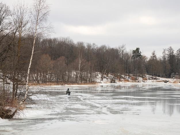 Pesca pericolosa sul ghiaccio primaverile umido. pescatore su ghiaccio fondente bagnato. russia.