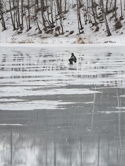 Pesca pericolosa sul ghiaccio primaverile umido. pescatore su ghiaccio fondente bagnato. vista verticale.
