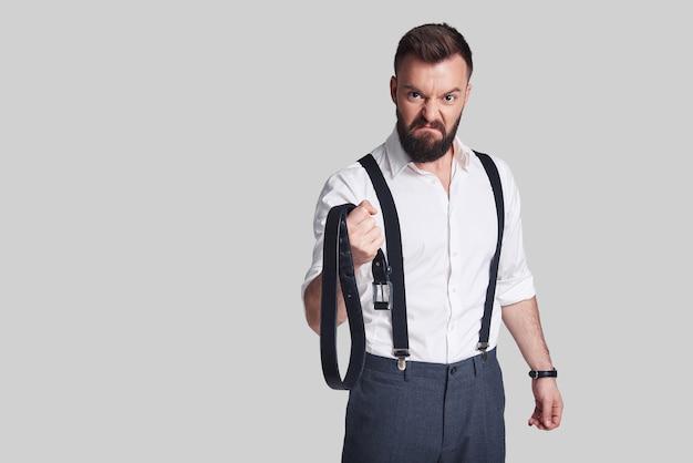 Uomo pericoloso. giovane arrabbiato in abiti da cerimonia che porta una cintura e guarda la telecamera mentre si trova in piedi su uno sfondo grigio