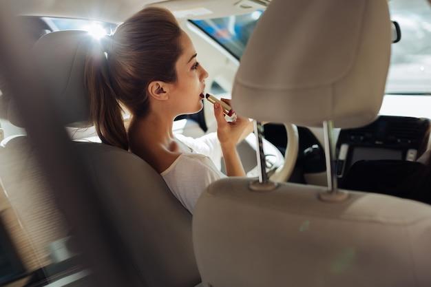 Multitasking pericoloso. attraente bella giovane donna seduta al volante e guida la sua auto mentre si trucca