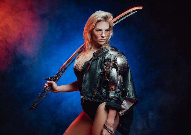 La combattente femminile pericolosa e allo stesso tempo bella dal futuro posa in uno sfondo scuro tenendo la sua lama sulla spalla.