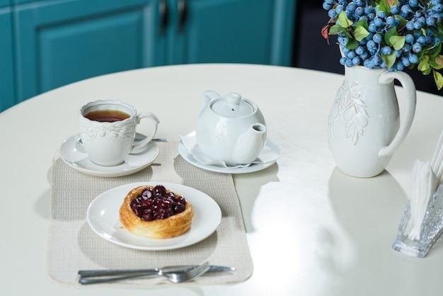 Torta danese con ciliegie e tè nero su un tavolo in un'accogliente caffetteria