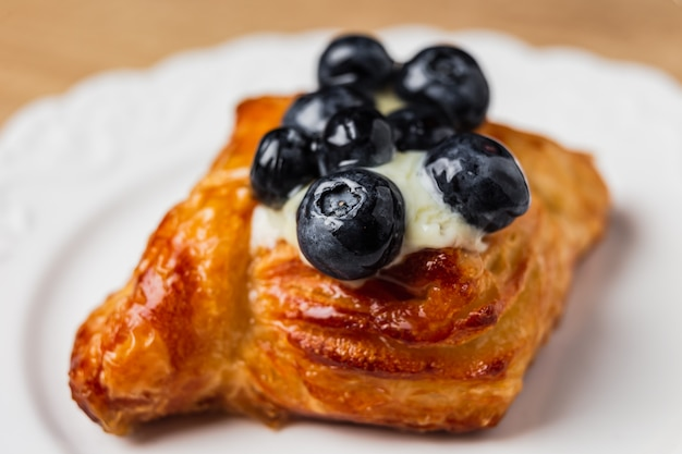Pasticceria danese con crema pasticcera e palude di mirtillo su un piatto bianco