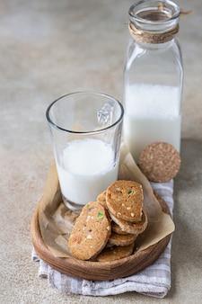 Biscotti al burro piccanti danesi con frutta candita, bastoncini di cannella e anice e bicchiere di latte.