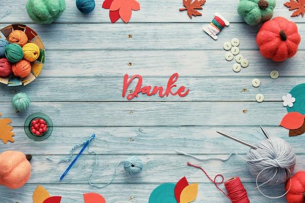 Danke significa grazie in tedesco. cornice decorativa composta da fasci di lana, gomitoli di filato, zucche decorative in feltro