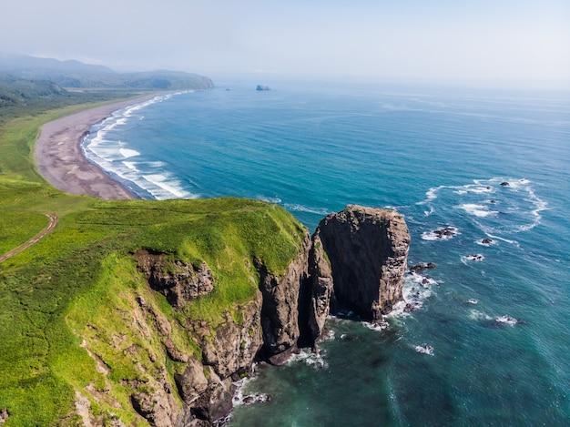 Spiaggia di sabbia di colore scuro quasi nero dell'oceano pacifico. le montagne di pietra e l'erba gialla sono su uno sfondo.