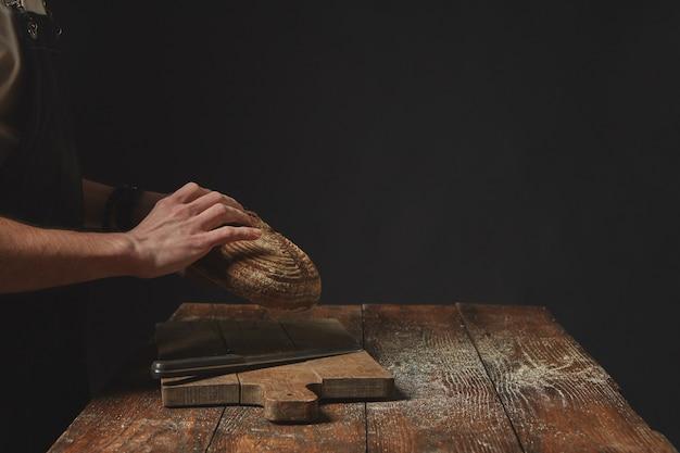 Su uno sfondo scuro mani di un uomo che tiene un pane rotondo