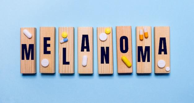 Su uno sfondo scuro, pillole multicolori e la parola melanoma su un blocco di legno. concetto medico