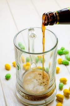 Birra scura che versa in una bottiglia di vetro