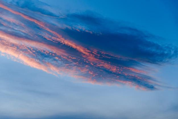 Cielo blu scuro prima del tramonto con bellissime nuvole fantastiche colorate sullo sfondo del tramonto