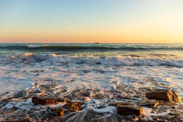 Onde blu scuro contro il bellissimo tramonto arancione sul mar nero, anapa, russia