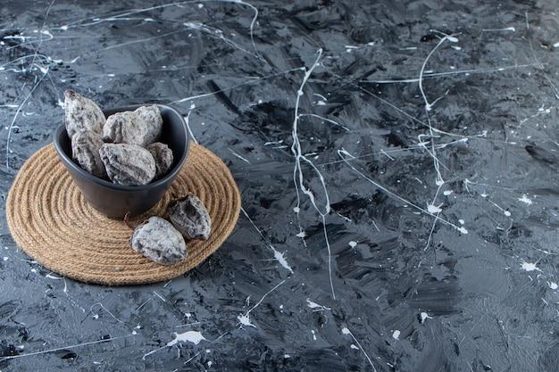 Ciotola scura di gustosi cachi secchi su fondo di marmo.