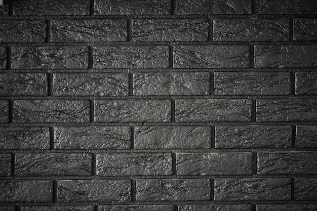 Sfondo di muro di mattoni scuri. parete in un ufficio moderno.