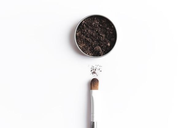 Ombretto marrone scuro in contenitore e ombretto o pennello per il trucco. concetto di trucco laici piatta