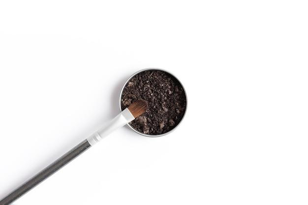 Ombretto marrone scuro nel contenitore e ombretto o pennello per il trucco