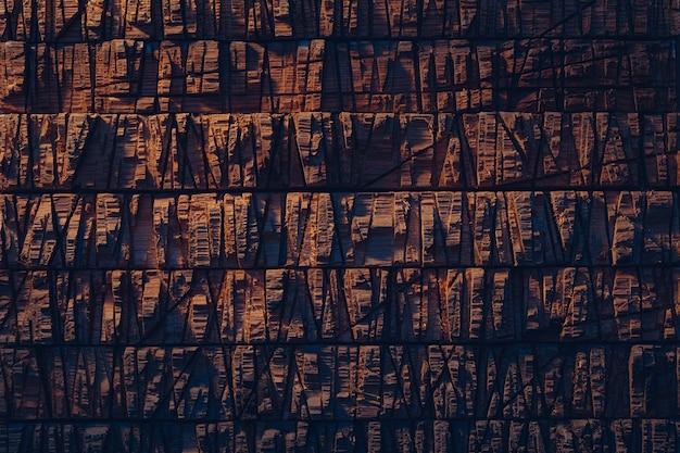 Priorità bassa di struttura di legno marrone scuro nella luce del tramonto.
