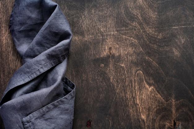 Struttura in legno marrone scuro con tovagliolo da cucina in cotone o asciugamano sopra. sfondo astratto. copia lo sfondo dello spazio