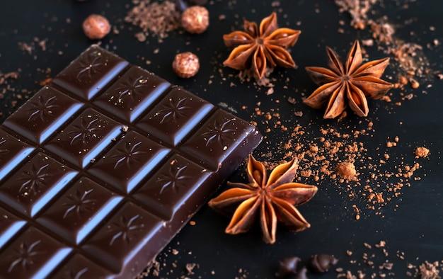 Barretta di cioccolato fondente con anice speziato, scaglie di cioccolato e primo piano in polvere