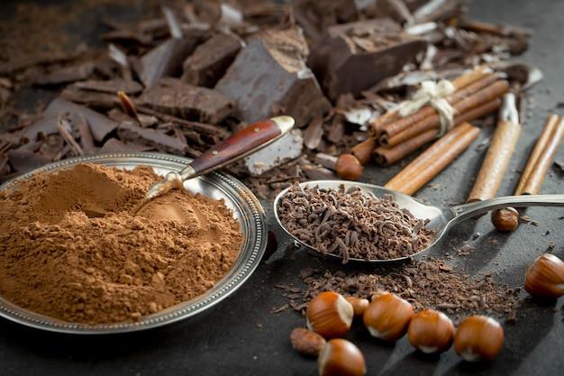 Cioccolato fondente in una composizione con fave di cacao e noci, su un vecchio sfondo.