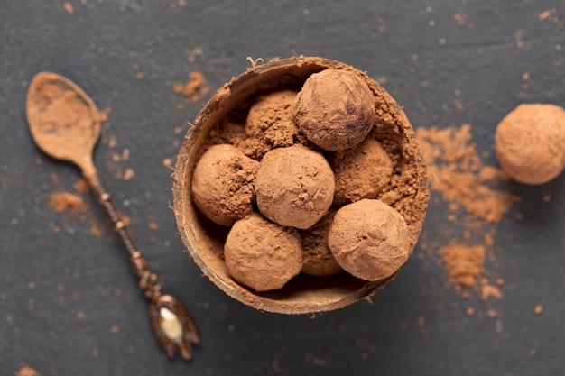 Tartufi di cioccolato fondente cacao in polvere in una ciotola di guscio di noce di cocco, vista dall'alto