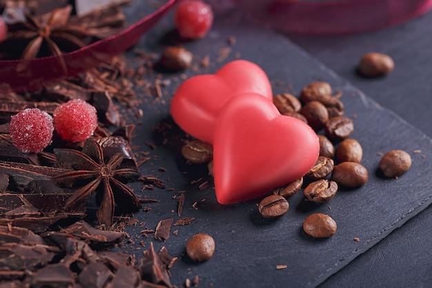 Tagliere di cioccolato fondente, chicchi di caffè tostati neri, bacche rosse, cioccolato rosso a forma di cuore, spezie di anice su tavola di ardesia su sfondo nero strutturale. concetto di pasticceria