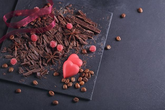 Tagliere di cioccolato fondente, chicchi di caffè tostati neri, bacche rosse, cioccolato rosso a forma di cuore, spezie di anice su tavola di ardesia su sfondo nero strutturale. concetto di pasticceria e dolci