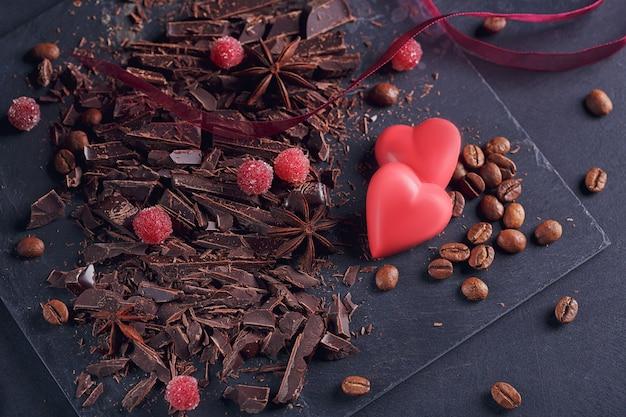 Tagliere cioccolato fondente, chicchi di caffè, bacche rosse, cioccolato rosso a forma di cuore, spezie di anice su tavola di ardesia su sfondo nero strutturale. concetto di dessert al cioccolato, confetteria e dolci